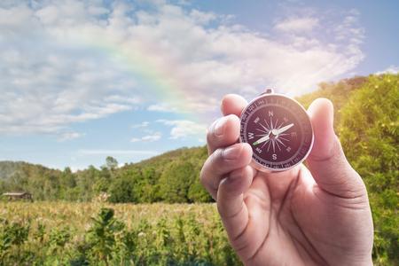 arco iris: Brújula en mano en la falta de definición de vistas a la montaña con el arco iris para el fondo