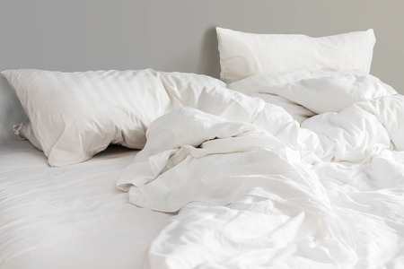 bed and white pillows with wrinkle blanket in bedroom, from sleeping in a long night. Stockfoto