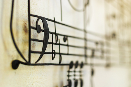 bass clef: F Clef Bass Clef old steel on the old wall with music note blur on background, vintage style Stock Photo