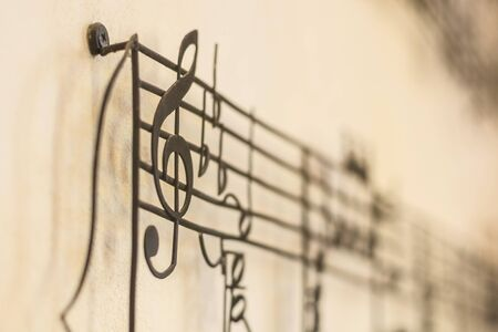minim: G Clef old steel on the old wall with music note blur on background, vintage style