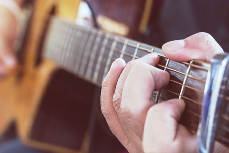 fingertips: Practicing in playing guitar, Hand of young men playing guitar chord C, selective focus on finger Stock Photo