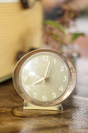 ultimatum: old nostalgic alarm on a table, Retro alarm clock on a table. Photo in retro color image style, vintage style