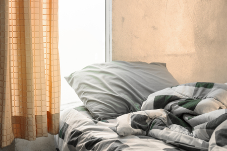 side lighting: Tartan pillow and blanket with wrinkle messy on bed in orange bedroom with lighting upper left side, from sleeping in a long night winter. Stock Photo