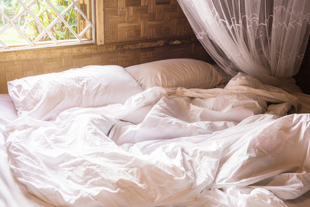 white pillow on bed and with wrinkle messy blanket in bedroom Thai lifestyles, from sleeping in a long night in winter. Stock Photo