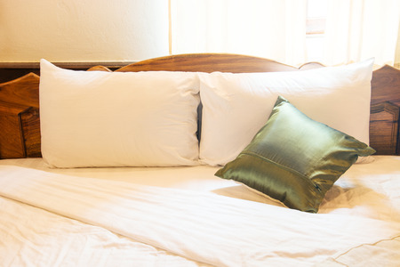 side lighting: pillow and blanket on bed in vintage wooden bedroom with lighting upper right side Stock Photo
