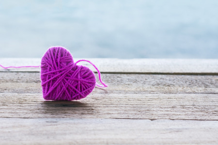 pink knitting wool in shape of heart on vintage wooden with bokeh soft light background Stock Photo