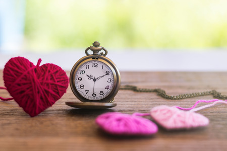 necklace antique style pocket watch with knitting wool heart on a wooden surface, symbol to express someone eternal love on special occasions i.e. Valentines day, Fathers & Mothers Day. Stock fotó
