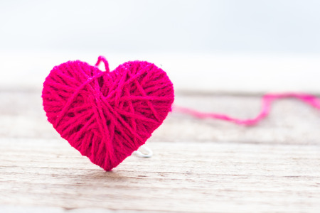 red knitting wool in shape of heart on vintage wooden with bokeh soft light background Stock Photo