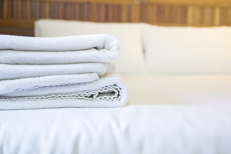 untidy: white towel on white mattress fabric, soft light in the morning