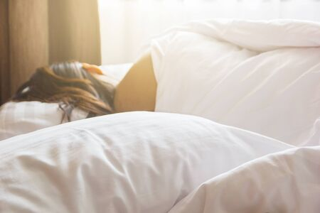 hotel bedroom: wrinkle messy blanket and white pillow in bedroom with blur image of woman sleeping, from sleeping in a long night. Stock Photo