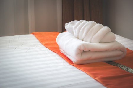 hotel bedroom: white bed with fresh white bath towel in the room
