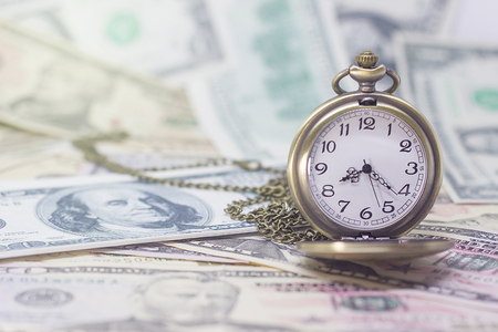 Classic pocket watch on dollar banknote, concept and idea of time value and money, business and finance concepts.