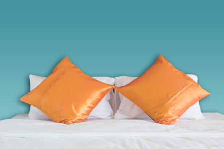 blue wall and orange pillow on white bed