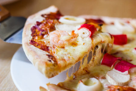 Hot seafood pizza slice with melting cheese on rustic wooden table. Stock Photo