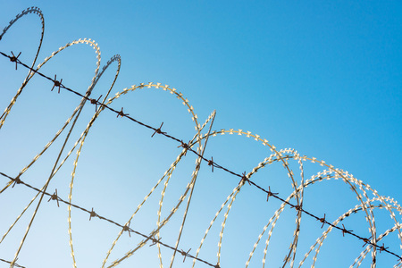 Barbed Wire Fence Used For Protection Purposes Of Property And Imprisonment, No Freedom, Barbed Wire On fence With Blue Sky To Feel Worrying.
