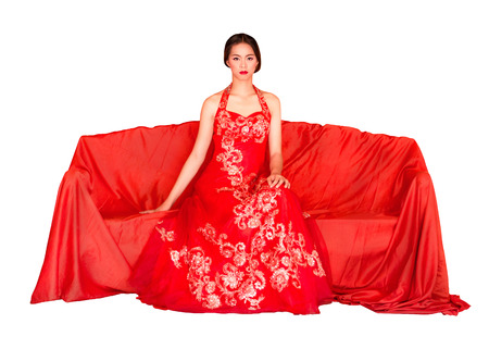 Asian Women (Chinese) In Costume Cheongsam (Mandarin Gown) Sit On A Red Couch, Isolated On White Background. Stock Photo