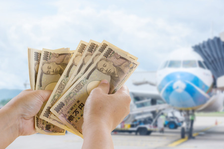 Yen Banknotes In Hand That Are Ready For Travel Tourism On Blurred Background, Tourist Business Idea
