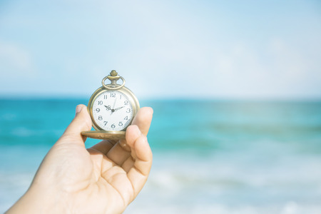 Hand Hold Old Pocket Watch With Blank Screen With Beautiful Sea Sand And Blue Sky In Background, Vintage Concept.