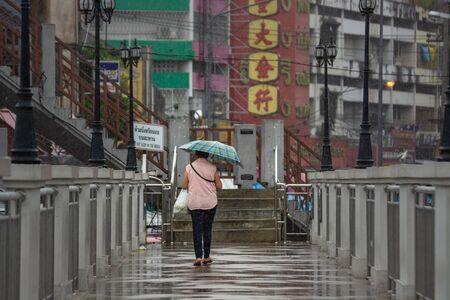 Chiang Mai, Thailand - June 10, 2018 : Women middle Age holding the umbrella while raining in the middle of a bridge at the Kad Luang. Chiang mai, Thailand Editöryel