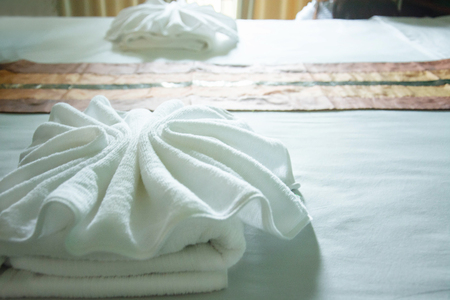 white towels on the bed with light from window.