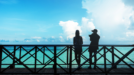 Silhouette of couples on the wooden terrace At Seaside and Sky, Lovers having tender moments summer vacation holidays, relationship and love concept Stok Fotoğraf