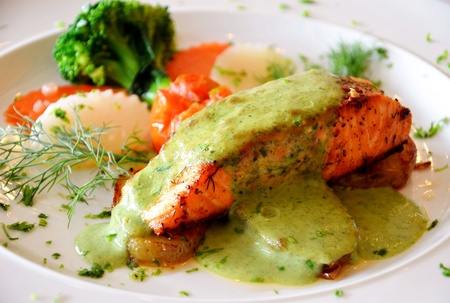 roasted salmon served with green sauce  photo