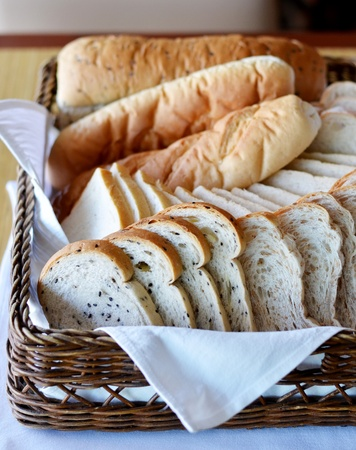 Arrangement of bread in basket on table photo