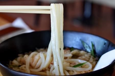 Udon noodle on chopsticks , noodle with shrimp tempura