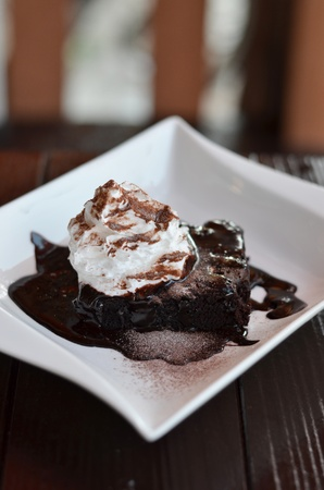 brownie cake served with chocolate sauce and whipped cream photo