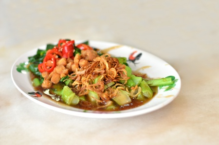 kale fried with oyster sauce  , topped with fried onion and red chili . photo