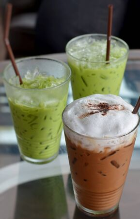 ice coffee and ice green tea on table photo