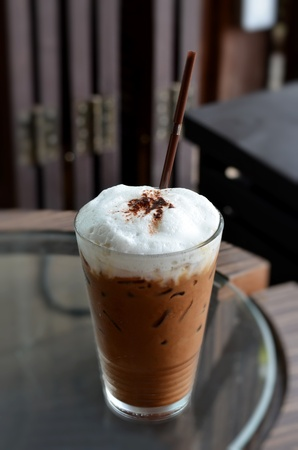Cold coffee drink with ice on a  table photo