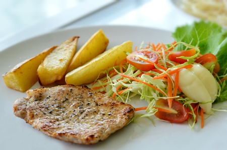 Grilled pork steak served with chips, potatoes and vegetables photo