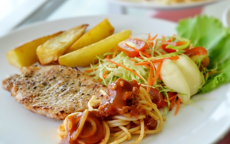 Grilled pork steak served with chips, potatoes and vegetables , macaroni photo