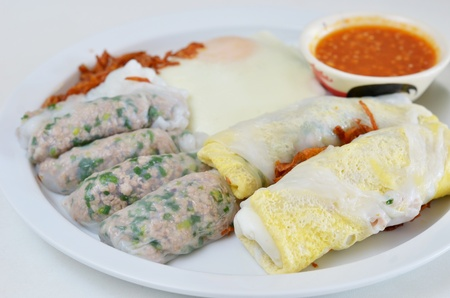 mixed vietnamese rice noodle rolls with a filling of pork sliced and egg ,  fried onion , served with spicy sauce photo