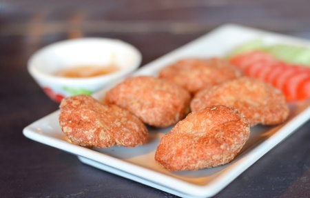 Spicy fried fish cake  Tod Mun Pla  served with cucumber , tomato and  sweet sauce   Stock Photo - 13588452