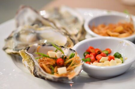 Oysters  with chilli and fried garlic , on white plate photo