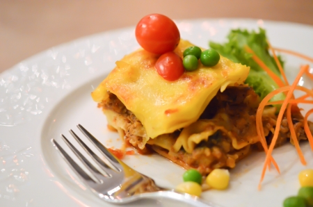Beef lasagna , served with tomato and fresh vegetable  photo