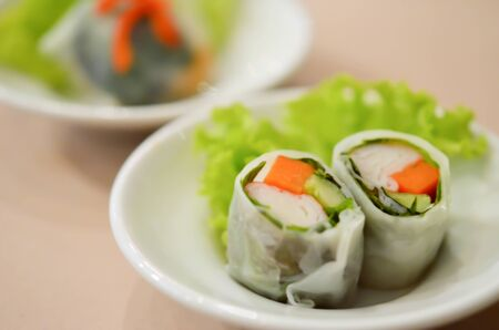noodle roll served with fresh vegetable on white dish photo