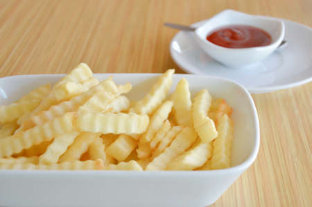 french fries on  white plate served with tomato sauce photo