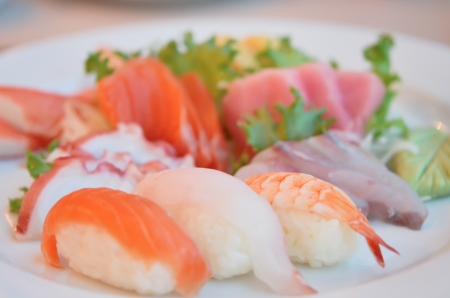 Mixed sushi and sashimi served on white plate Imagens
