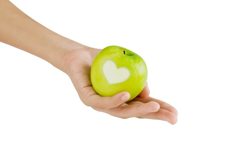 hand and green apple with  heart shape on white background