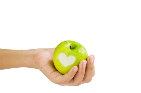 hand and  apple with  heart shape on white background photo