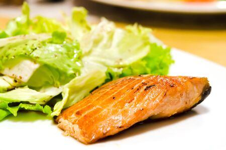 salmon steak with fresh lettuce on dish  photo
