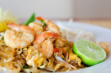 Stir fry noodles with shrimp , egg  and  vegetable served with fresh lemon photo