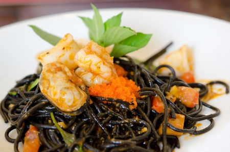 Black spaghetti with green mussel , fish eggs and shrimp  on white dish photo