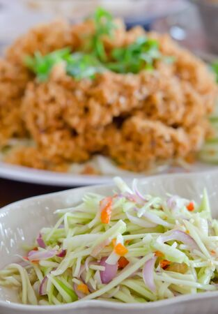 green mango salad  and vegetable served with crispy catfish , spicy and sour photo