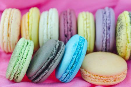 close up colorful  french macaroons   on  pink fabric photo