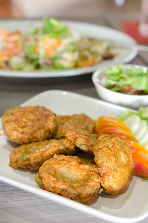 Spicy fried fish cake  Tod Mun Pla  served with cucumber and tomato on dish , thai food photo