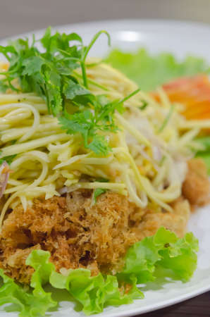 close up Crispy catfish salad with green mango and vegetable on white dish photo